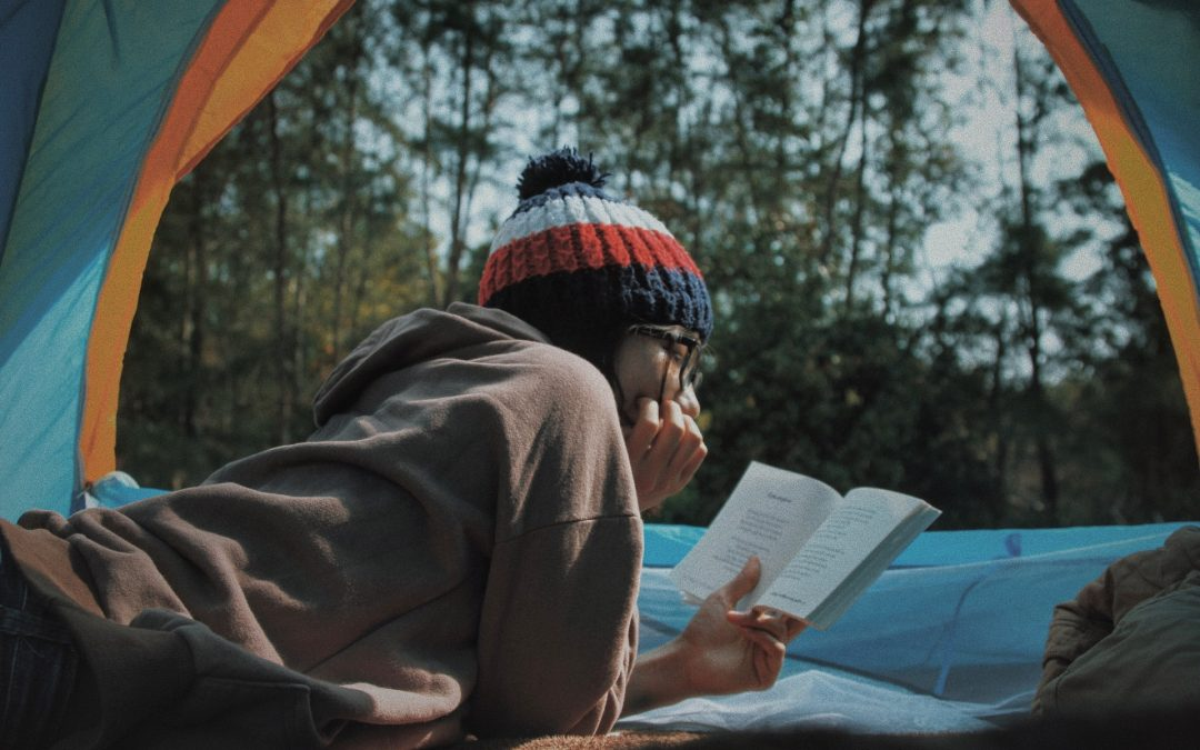 Woman reading about the way to protect books when camping